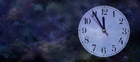 12 o'clock: Its Nearly New Year - Wide night sky background with a clock face showing five minutes to midnight on the right side and copy space on left Stock Photo