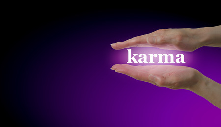 karmic: Your Karma is in Your Hands - Female hand parallel with the word Karma floating between on a magenta and black background with plenty of copy space