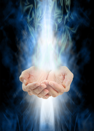 energy channels: Receiving healing  -  Female cupped hands with white energy streaming  in from above and below on a swirling misty blue and green energy background