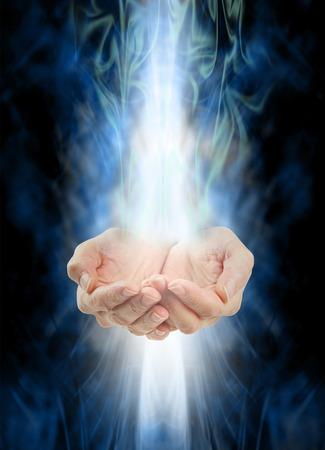 Recepción de la curación - manos ahuecadas Mujer con energía blanca que entraba desde arriba y abajo en un fondo brumoso energía azul y verde que rota Foto de archivo