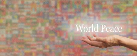 Holding out for World Peace - Female hand outstretched with the words WORLD PEACE floating above, on a wide multicolored rustic stone effect background made up of softly faded national flags Stock Photo