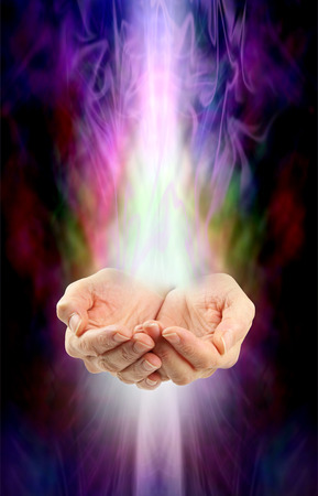 energy channels: Receiving healing  -  Female cupped hands with white energy streaming  in from above and below on a swirling misty multicolored ethereal energy background