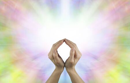 wholeness: The Circle of Eternal Life - Female hands making an O shape with a vibrant burst of white light energy behind filled by a rainbow colored butterfly shape and plenty of copy space
