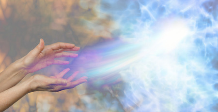 Soul midwife - female hands on a darkness to light background and a soul energy formation moving out towards the light depicting soul release Stock Photo