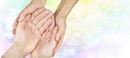 Create ripples of kindness - female hands gently holding male hands in cupped position on a subtle rainbow colored water ripple background fading to white with plenty of copy space