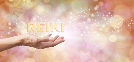 heal: Golden Reiki Healing Energy Share    - Female with outstretched hand palm facing up and the word REIKI hovering above  on an ethereal golden bokeh and sparkles background and white light Stock Photo