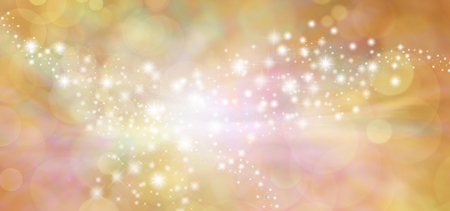 wide: Golden starry glitter warm toned bokeh background banner - Wide autumnal orange and gold  sparkling glittery star speckled background with a whoosh of movement in the middle