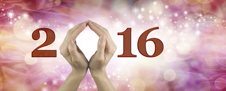 make a gift: Welcome 2016 with both hands - Female using both hands to make an O in the word 2016 on a warm red and pink colored starry bokeh  background Stock Photo