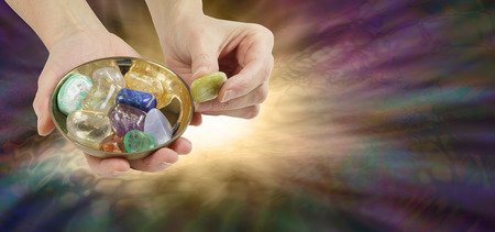 tumbled: A Stone Just for You - Female offering a yellow stone from a brass dish containing a selection of tumbled crystal stones on a  wide multicolored background with copy space and ethereal light burst Stock Photo