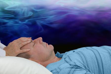 psiquico: Equilibrar el chakra del tercer ojo - sanador Mujer de pie con las manos colocadas suavemente en la frente del hombre canalizar la energía curativa de chakra del tercer ojo con una niebla que se mueven por encima de la formación de la energía