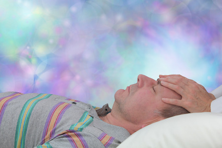 healer: Enjoying a Relaxation Therapy Session - Female healer with hands gently placed on mans forehead channeling healing energy to third eye chakra with a dreamy blue bokeh background and copy space