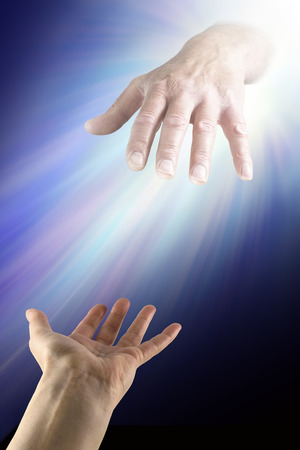 reaching up: Reaching out for Divine Help - a female hand with palm open reaching up to a glowing masculine hand emerging from a bright light on a dark background