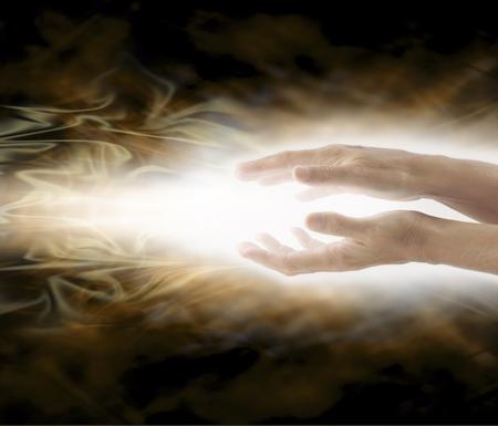 Stralend Reiki Healing Energy - Vrouw met handen die evenwijdig verzenden helende energie op een wervelende mistige etherische goudbruin achtergrond en veel ruimte kopie