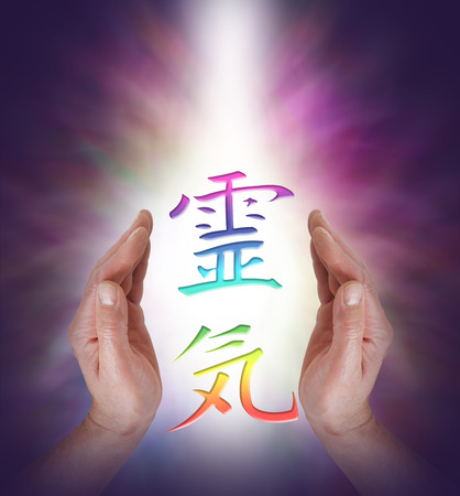 energy healing: Embracing the Art of Reiki Energy Healing - Reiki Kanji Symbol floating between Male healers hands with a shaft of white light behind on a dark background