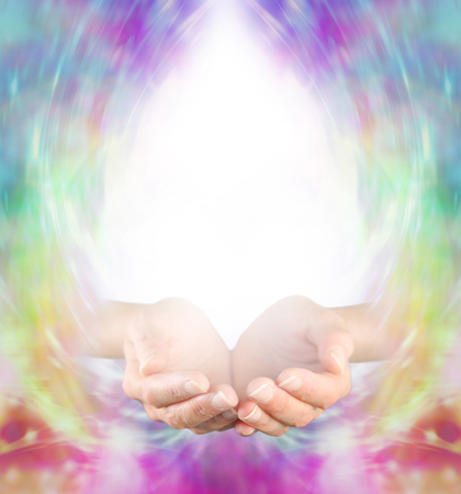 energy channels: Healing Message Board Background - Female cupped hands with white light above forming a large copy space with a multicolored energy formation border