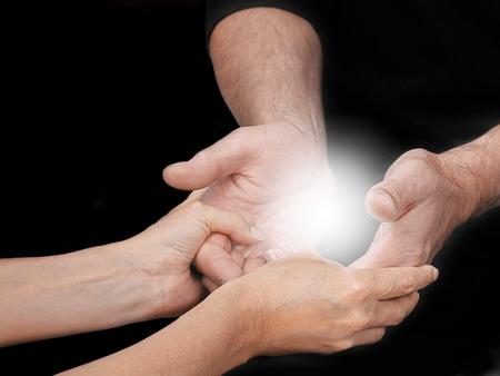 psiquico: Compartir una experiencia Energía - Mentor sanación femenina que sostiene estudiantes de sexo masculino con las manos abiertas un orbe de energía de la luz brillante entre en un fondo negro y copia espacio