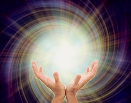 manos: La inspiración sagrada - manos ahuecadas abiertas hacia una estrella de oro en forma de luz que emerge de una formación en espiral multicolor sobre un fondo azul oscuro añil que representa la inspiración divina