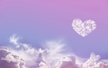 Love is in the Air - Wide Blue and Pink Sky Background with fluffy clouds along the bottom and one large isolated Love Heart Shaped cloud formation above on right hand side with plenty of copy space