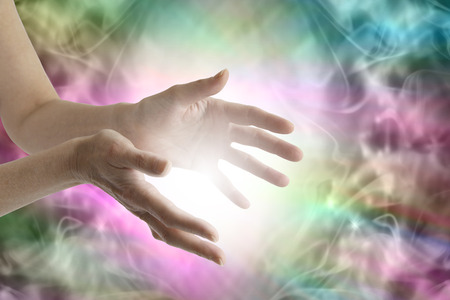 Beaming healing energy - Outstretched female healing hands with white light between and a vibrant multicolored flowing energy field background Stock Photo