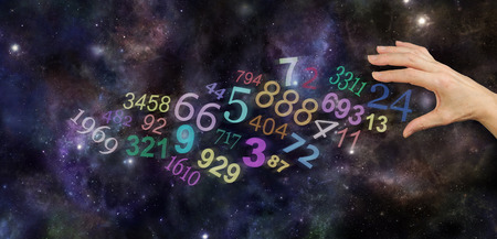 pseudoscience: The Universal Significance of Numbers - female hand about to take number 24 among a group of scattered multicolored transparent numbers on a wide deep space background with copy space Stock Photo