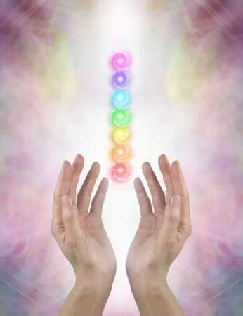 healing with chi: Sending Chakra Healing Energy - Female parallel hands facing upwards with white energy and the Seven Chakras floating above on a pink ethereal energy formation background Stock Photo