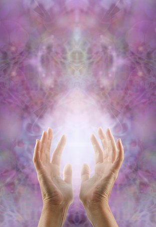 Sensing Sacred Healing Energy -  female hands reaching up with healing energy light between on an intricate symmetrical sacred lilac pink colored pattern background