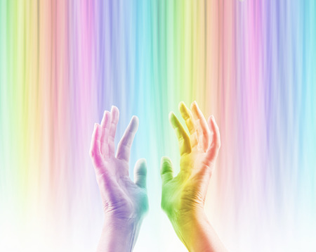 color therapy: Absorbing Color Light Therapy - Female hands reaching up into rainbow colored light streaming down causing hands to become rainbow colored whilst absorbing the colored light Stock Photo