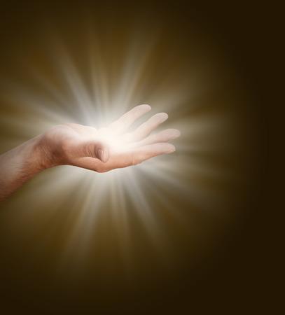 Öffnen Sie eine männliche Hand mit Palme mit Lichtenergie auf einem dunklen, warmen braunen Hintergrund glüht.