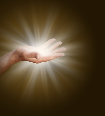spiritualism: A male hand with palm open  glowing with light energy on a dark warm brown background. Stock Photo