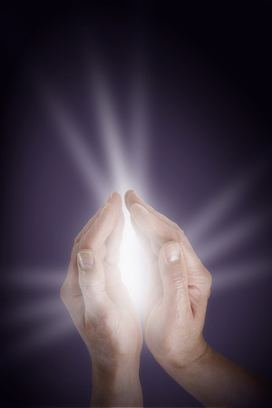 spiritualism: Male cupped hands with  glowing light energy streaming out on a dark warm purple background