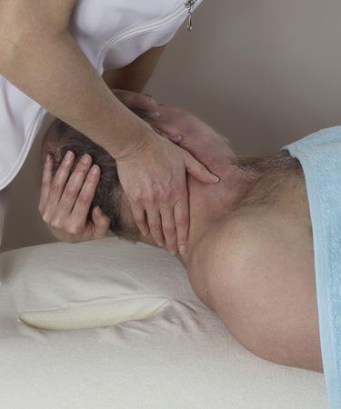 masaje deportivo: Estirar los músculos del cuello - los deportes femeninos de elevación terapeuta de masaje y girando a la cabeza de un paciente de sexo masculino maduro izquierda para estirar y soltar los músculos del cuello Foto de archivo