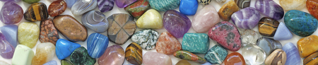 tumbled: Healing Crystal Website Banner - a wide strip of multicolored tumbled gemstone crystals
