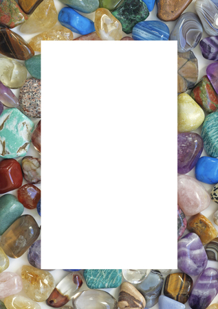 filled out: Healing Crystal Gemstone Filled Border  - A solid portrait oriented rectangle filled with multicolored tumbled stones with the center cropped out providing an empty white central background Stock Photo