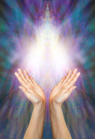 universal love: Goddess Healing Energy - a pair of female hands reaching up towards a beautiful angelic light form on a multi colored blue and purple background with plenty of copy space
