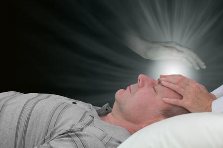 Channeling healing met een spirituele gids - gelegd op het voorhoofd van een mannelijke patiënt met een etherische spookachtige geest hand boven zweven vrouwelijke handen en een gloed van heling lichtenergie op een donkere achtergrond