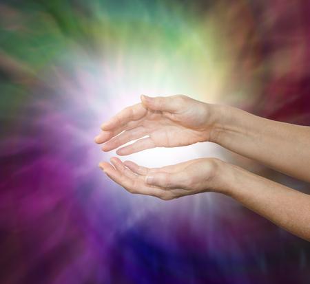 universal love: Sintiendo la energ�a de curaci�n sutil - manos femeninas celebradas suavemente ahuecadas con una luz blanca entre en un torbellino de colores calientes ricos arremolinadas y un mont�n de espacio de la copia Foto de archivo