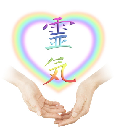 complementary therapy: Sharing Reiki healing -   Female cupped hands with a soft focus heart shaped rainbow and a rainbow colored Japanese Reiki Symbol floating above on a white background Stock Photo