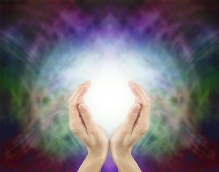 Pranic Healing Energie - weibliche Hände gehöhlt um eine Kugel der hellen Energie an einem schönen feinen mehrfarbigen Energiefeld Hintergrund mit viel Platz kopieren