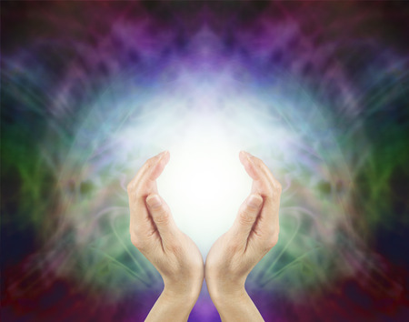 healing chi spiritual: Pranic Healing Energy - female hands cupped around a ball of bright energy on a beautiful subtle multi colored energy field background with plenty of copy space