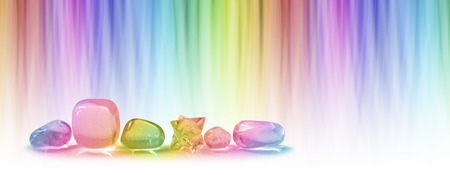 prana: Healing crystals and color healing website header -  A  row of five tumbled healing crystals and a merkabah against a linear graduated chakra rainbow color background with plenty of copy space