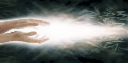 universal enlightenment: Beaming Reiki Healing Energy - Female parallel hands with a beam of bright white energy flowing outwards on a wide ethereal grey blue energy formation background