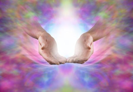 manos abiertas: Enviando energía curativa sagrada - Hombre manos en el gesto abierto con estallido de luz blanca entre en un bello fondo etéreo formación de energía multicolor con un montón de espacio de la copia