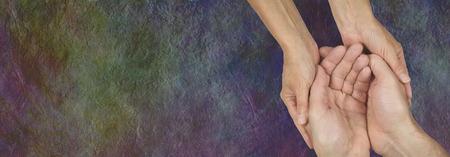 Verzorging voor mensen in nood - Rustieke donkere steen effect Wide achtergrond met een vrouwelijke handen cupped rond een mans handen die een verzorger uitbeeldt