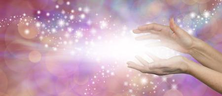 psiquico: La magia de curación - manos paralelas femeninos con un estallido de luz blanca entre destellos y hacia el exterior que fluyen en un fondo púrpura de color rosa con un montón de espacio de la copia