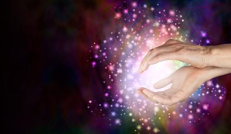 超自然的な癒しのエネルギー - 女性をセンシング少女カップいっぱい白い輝き光の周りと深い色の背景の美しいキラキラ ボールと手