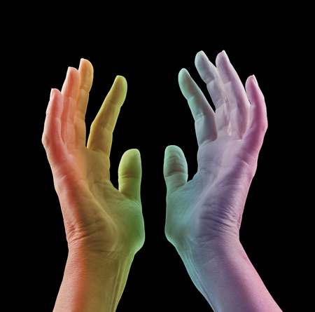reaching up: Absorbing Color Light Therapy - Female hands reaching up with colored light projected onto skin in rainbow range of colors - red orange, yellow, green blue, magenta, against a black background Stock Photo