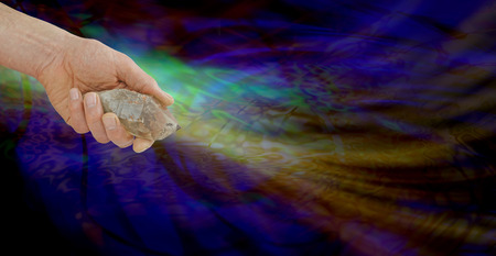 vibrations: Energised Smokey Quartz Wand - Male Crystal Healer holding large terminated Smokey Quartz on wide multicolored dark background with ethereal energy formation display and copy space
