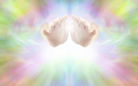 psychic: Life Force Healing Energy - female hands emerging from vibrant rainbow colored energy field with white light beneath and plenty of copy space