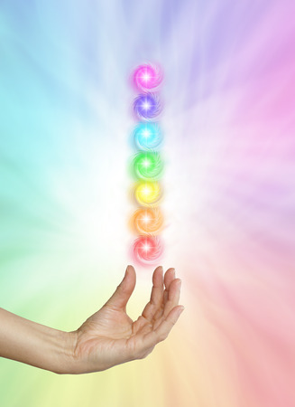 chakra energy: Seven Spinning Chakras on Rainbow colored background - Female healing hand outstretched with palm upwards and seven chakras hovering above on a rainbow colored background Stock Photo