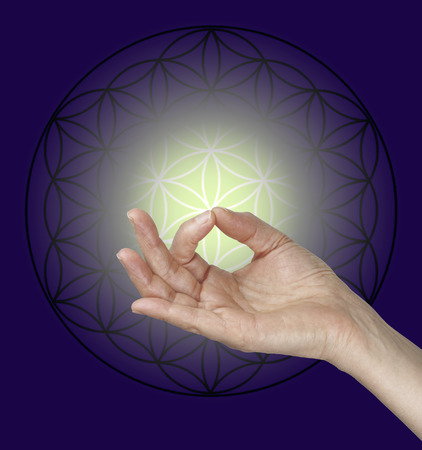 hand position: Gyan Mudra and the Flower of Life Symbol - female hand making Gyan Mudra hand position with the Flow of Life symbol in the background and a pale lemon glow surrounded by dark blue